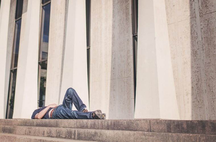cansancio, hombre sentado en escaleras, escalinatas, edificio blanco, carga laboral extrema, demasiado trabajo