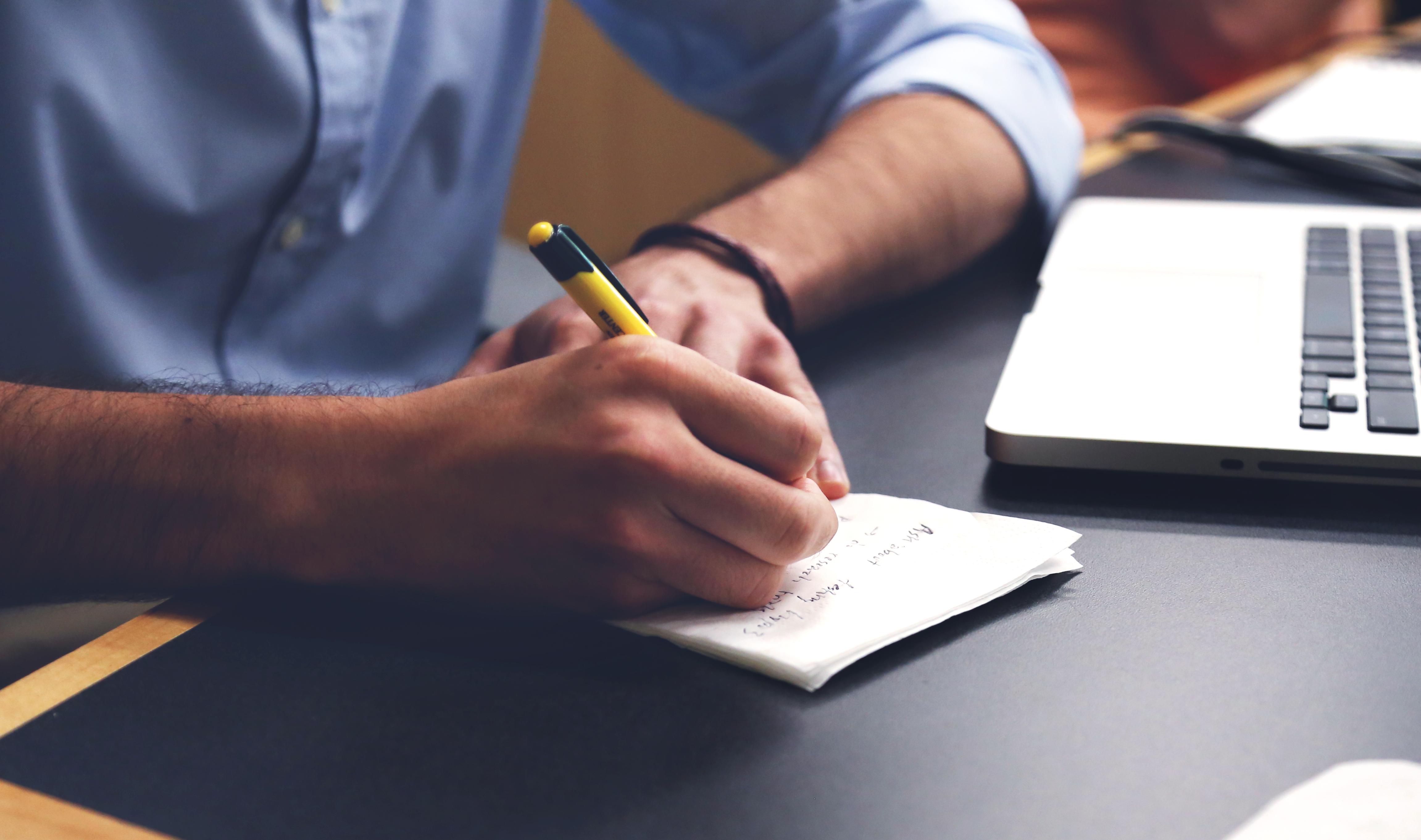 entrevista, selección laboral, escribiendo, notas, cuaderno, camiza azul, esfero amarillo, oportunidad laboral, selección laboral