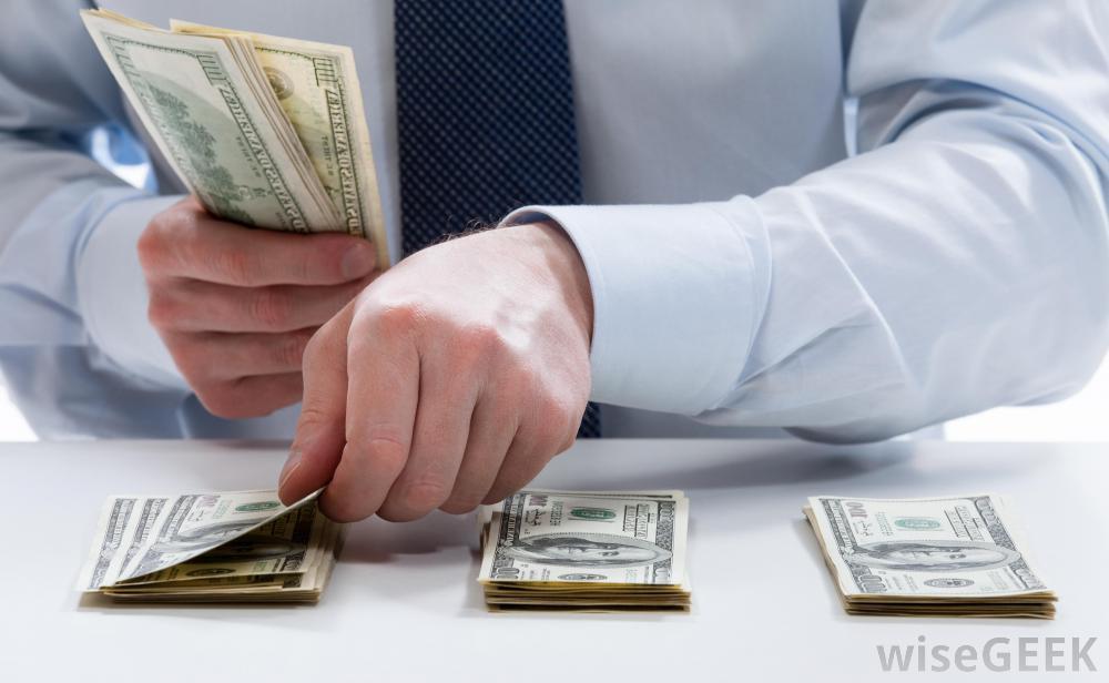 man-in-tie-stacking-three-piles-of-large-bills